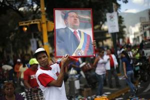 A supporter of Venezuela's President Hugo Chavez holds up a portrait of him while attending a rally in Caracas